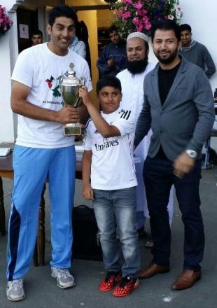 Zeeshan Qasim accepts the winners' trophy on behalf of Keighley RZM