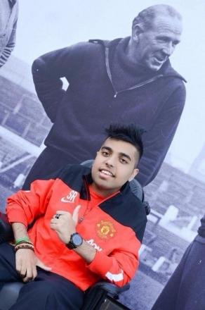 Sohail Rehman in his Manchester United tracksuit, in front of a photograph of club legend Matt Busby.