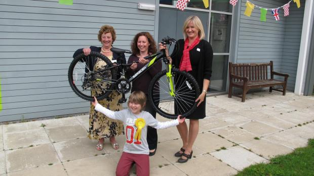 Luke Westerman receiving his bike, with, from left, Coun Gladys Emmott, his mum Charlotte and Helen Willis of Redrow Homes