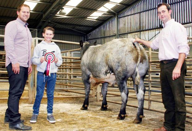 James Robertshaw, left, of  Keelham Farm Shop, with his 12-year-old son Harley and prime cattle champion Simon Bennett