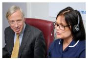 Earl Howe using the secure video link in the Telehealth Hub at Airedale Hospital to speak to a patient, accompanied by telehealth sister Alex Blake