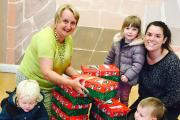Emma Ibbotson, right, of Country Kids, and youngsters hand over the shoeboxes to Eva Phillips, of Stanbury School