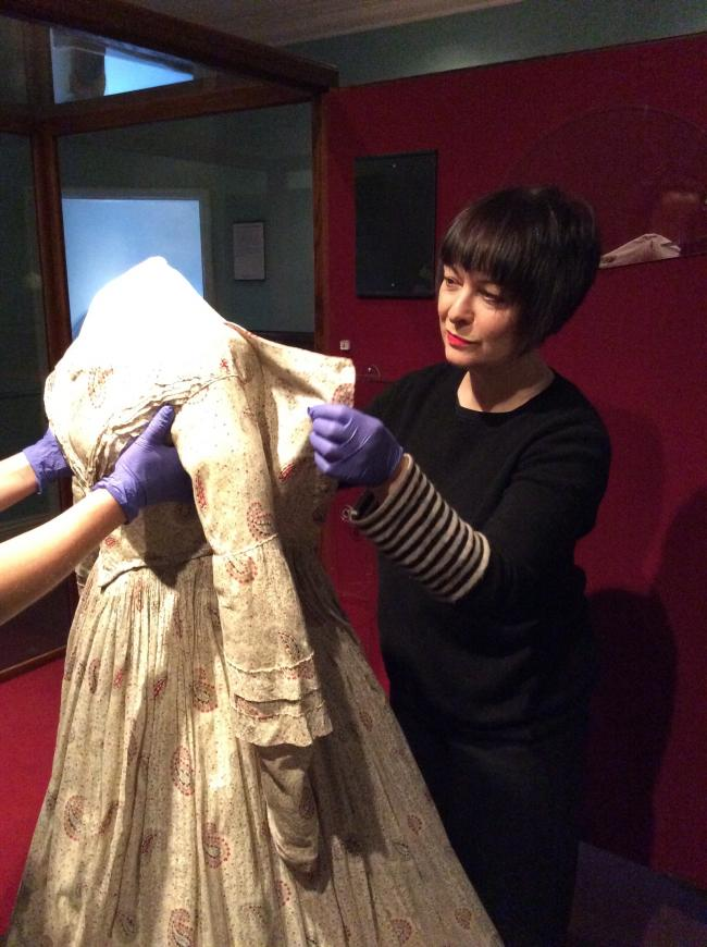 Principal Curator Ann Dinsdale carefully removes Charlotte Bronte's dress from display at the Bronte Parsonage Museum