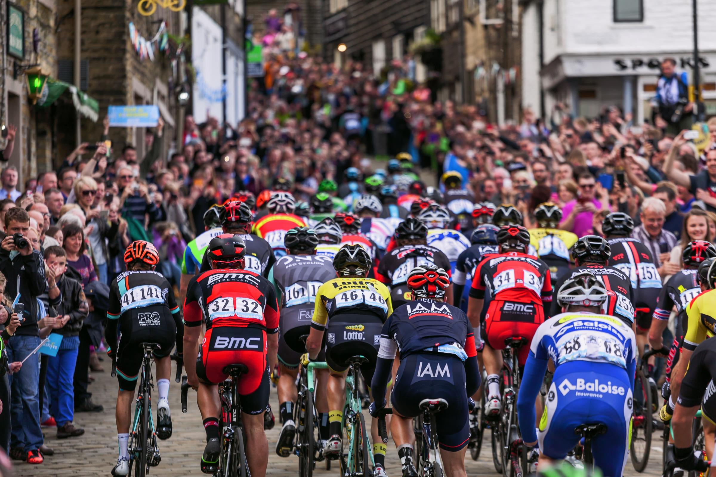 Riders in a previous Tour de Yorkshire head up a packed Haworth Main Street, which will again form part of the route this year