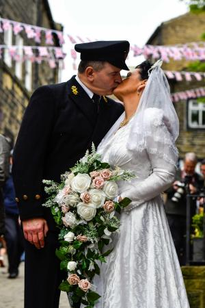 Keighley News: Sealed with a kiss: Nigel and Alex Richards were among thousands of people who descended on Haworth for the village's massively-popular annual 1940s Weekend.