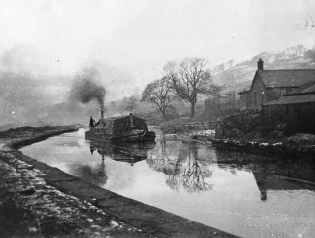 A view of a laden barge on a wintry Leeds and Liverpool Canal taken from the Bar Lane bridge, probably in the 1920s.