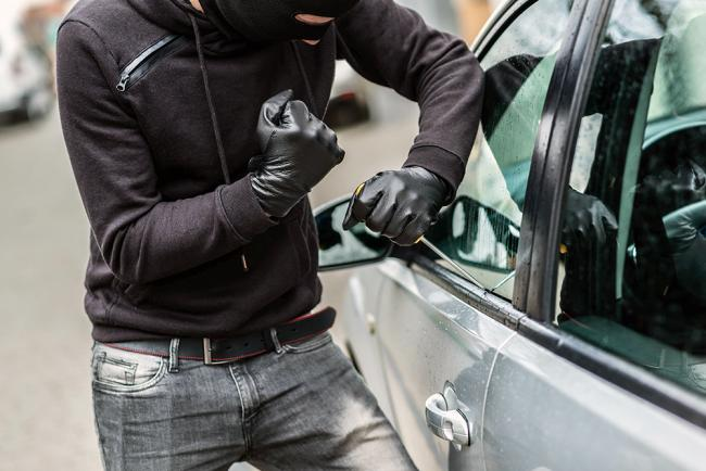 The man dressed in black with a balaclava on his head trying to break into the car. He uses a screwdriver