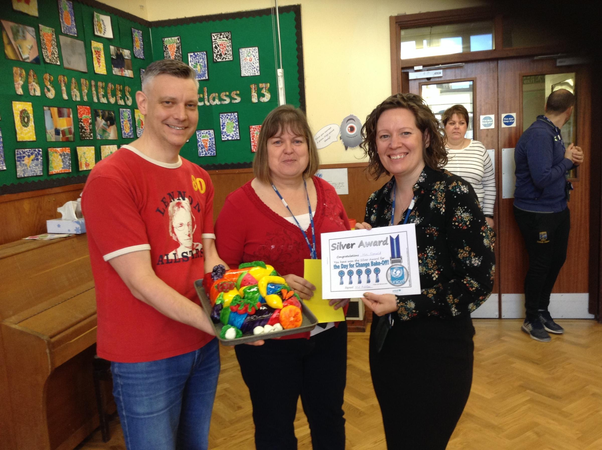 Teacher Carla Donald, who came second in the Glusburn Primary School UNICEF bake-off, pictured with judge Annette Waggett and Richard Hunt