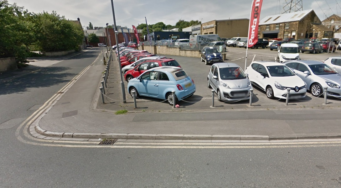 The tight bend on Longcroft, which a councillor suggests can be alleviated by Bradford Council buying part of the disused former Pentagon car dealership site and widening the road. Image from Google Street View.