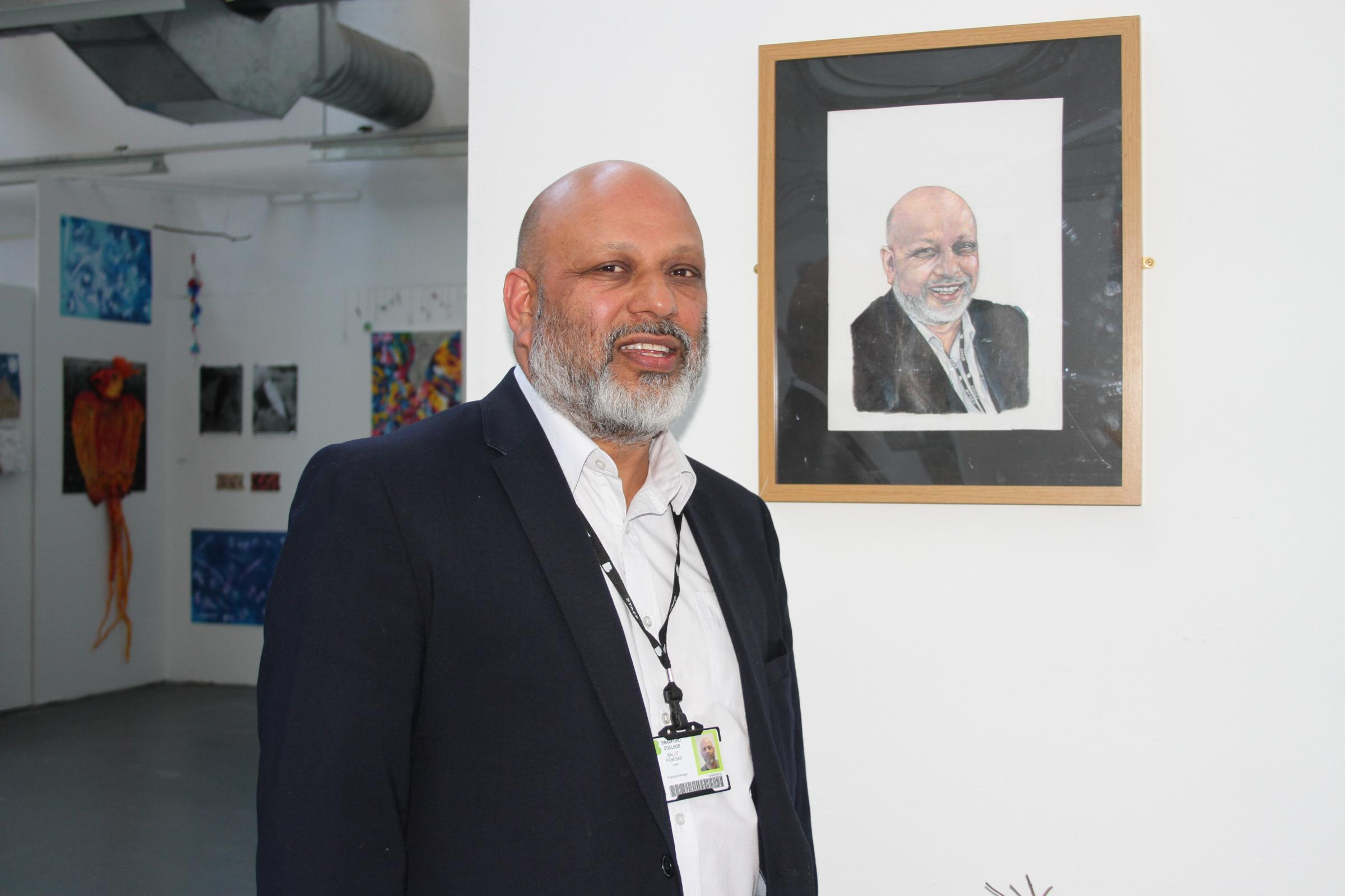 Baljit Panesar stood by the portrait of himself