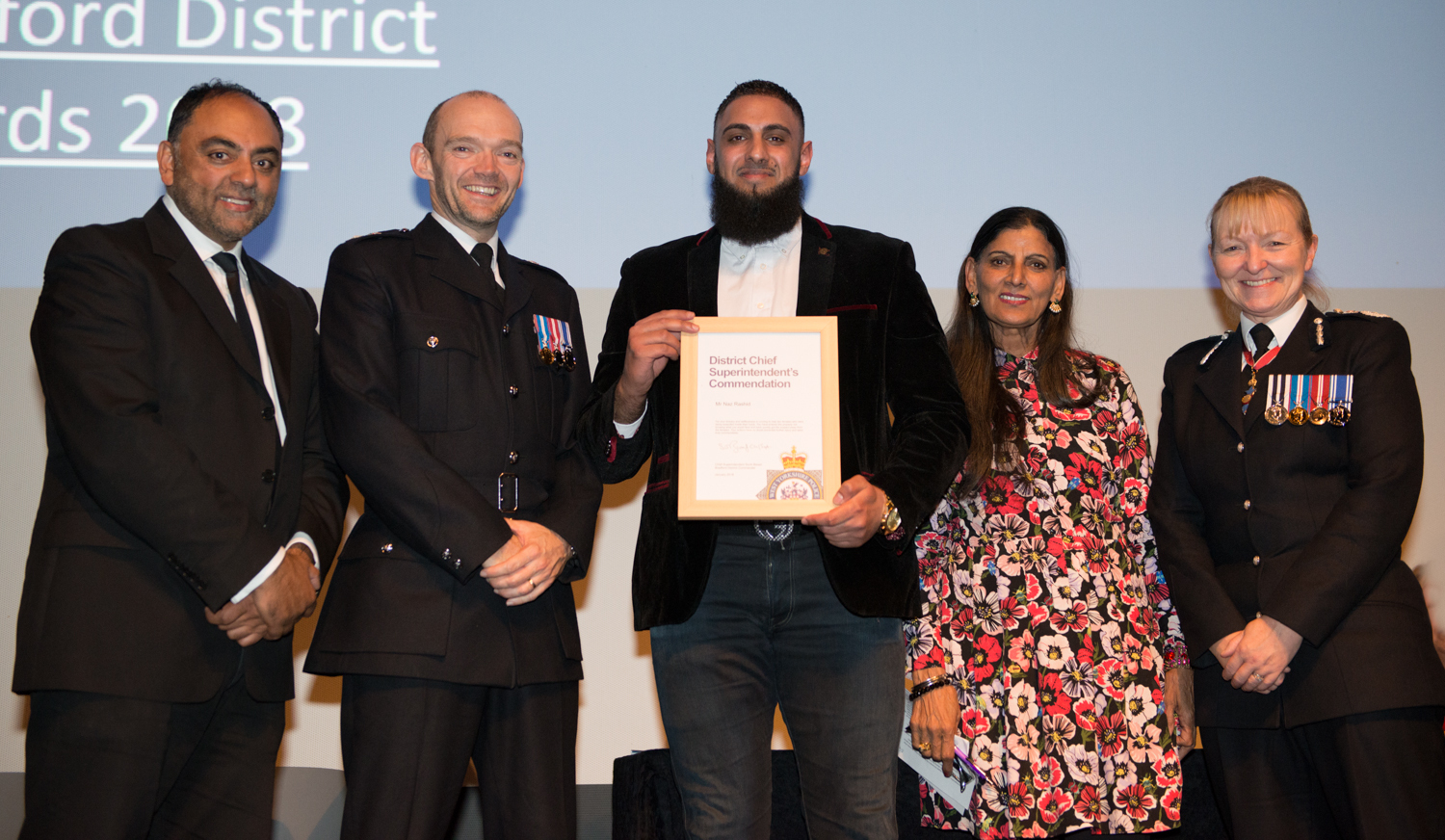 Keighley man Naz Rashid with officers and community figures at the Bradford District Policing Awards