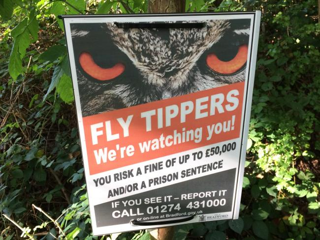 An anti flytipping warning poster in Elam Wood, Keighley